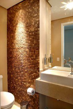 """Este lavabo de 1,55 m², ambientado pela arquiteta Cristiane Schiavoni tem iluminação direta e indireta que cria um clima intimista ao espaço. """"A iluminação é um recurso barato que dá muito efeito na decoração de banheiros e lavabos. Nestes ambientes pode se utilizar pendentes, arandelas, iluminação de piso e atrás do espelho"""", comenta a profissional. A parede revestida com pastilhas de coco dá aspecto rústico ao ambiente."""
