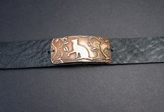 Rustic Antiqued Cat Bracelet. Made entirely in my studio using my original Bronze Cat Link. I then added it to a soft black leather cuff. The whole thing is then darkened with a deep patina to give it an aged look.  Total length of bracelet is 8 1/2 inches long Adjustable to snaps at 7 1/4 and 8 1/4 inches   All of my recycled metal jewelry is made from Metal Clay. The Fine Silver, Sterling Silver, Bronze and Copper originate from recycled fine metal particles suspended in an organic binder…