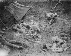 Half a dozen dead German soldiers strewn about the wreckage of a shell hole, 31 July 1917.