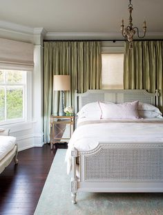 Beautiful bedroom features a grey french cane bed dressed in white and dusty pink bedding next to a mirrored nightstand with gold trim topped with a gray baluster lamp atop a gray and turquoise flocked rug placed in front of windows dressed in green silk curtains.