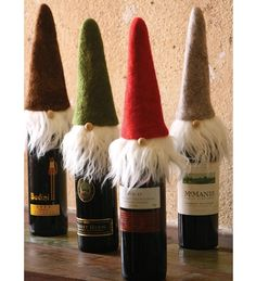 Too cute!!! Set of 4 Felt Santa Wine Toppers with wispy beards, little noses and felt hats in different colors.