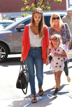 50 Unparalleled Street Style Looks Courtesy of Jessica Alba: Jessica tucked a white tee into floral denim, then spiced things up with a coral bag in West Hollywood. : Even on a casual coffee run in LA, Jessica looked stylish in brown riding boots, a black Bulgari bag, and tortoise sunglasses. : Jessica Alba rocked a pair of high-waisted jeans with a striped tank and a red cardigan in LA.