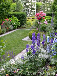Perennial beds filled with delphiniums, hollyhocks, and viburnum line the charming pass-through that connects the entry garden to backyard areas, including a bluestone patio. - Photo: Matthew Benson