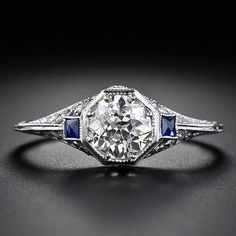 This exceptionally lovely vintage engagement ring displays a harmonious combination of Art Deco geometry and Edwardian delicacy. A bright .79 carat European-cut diamond beams from an octagonal setting flanked on each side by a small, deep blue, square French-cut sapphire (synthetic) - while the gallery below displays a charming, feminine filigree foliate design.