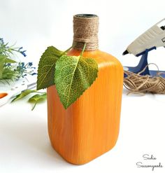 Wrapping the bottle neck of a hand painted glass bottle pumpkin with jute twine by Sadie Seasongoods / www.sadieseasongoods.com