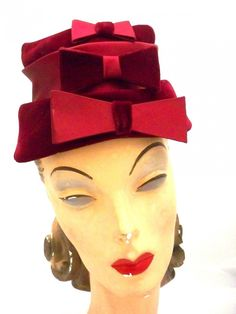 """Deep claret red velvet & satin makes up this little """"tower"""" of a hat, which is comprised of three sections, each with a bow, alternating velvet and satin. It is a size 22"""", which is medium, and it is"""