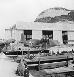 Busy scene by the slipway at North Front, Gibraltar. In the foreground various RAF marinecraft undergo maintenance. Parked behind them are shrouded Consollidated Catalinas of No. 202 Squadron RAF, while in front of the hangar, an engine service is undertaken on Short Sunderland Mark I, L5798 'KG-B', of No. 204 Squadron RAF based at Bathurst, The Gambia. Between 1941and 1944, this unit regularly escorted Allied convoys between Gibraltar and West Africa.