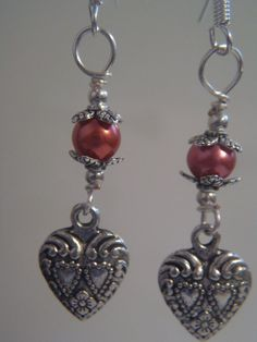 Engraved hearts hanging from lustrous glass pearls.