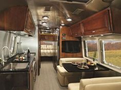 Large windows spanning the dining nook allow residents to enjoy the scenery while eating.  Airstream Trailer - 2015 Airstream Campers - Country Living