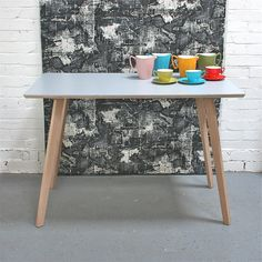 Made by Winters Moon, this table is a contemporary take on formica tables of the past.    Using Formica in the perfect steel grey, the table has a