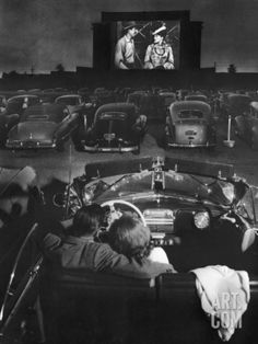 Young Couple Snuggling in Convertible as They Watch Large Screen Action at a Drive-In Movie Theater Photographic Print by J. R. Eyerman at eu.art.com