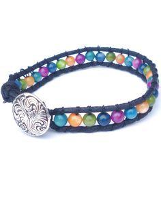 Deze armband is gemaakt van zwart waxkoord en halfedelstenen in allerlei kleuren. De armband sluit met een zilverkleurige knoop.  Lengte circa 18,5 cm.