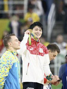 男子個人総合を2連覇し、金メダルを手に笑顔の内村航平(中央)。左は2位のオレグ・ベルニアイエフ、右は3位のマックス・ホイットロック(10日、ブラジル・リオデジャネイロの五輪アリーナで)=関口寛人撮影