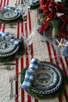 A coastal Christmas table!!! Bebe'!!! Love the use of the blue coastal design china with the festive red and green centerpiece!!! Bebe'!!! Love the use of a red and white quilt instead of  table cloth!!!