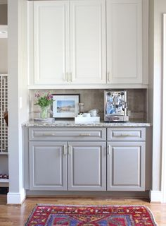 Two toned kitchen cabinets.....white on top, gray on bottom with neutral backsplash and granite counter tops.