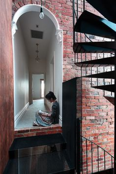 Brick wall with open halls to glass inclosed courtyard or greenhouse.  Andrew Maynard Architects