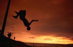 Boy doing backflip at sunset on Ipanema beach. #lpcelebrazil