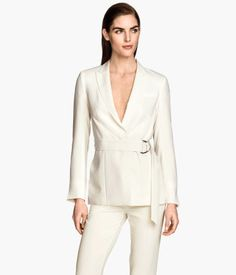 Fitted jacket in woven fabric with a belt at waist. Decorative chest pocket, hook-and-eye fastener at front, and vent at back. Slits at cuffs. Lined.