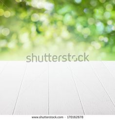Empty table in a sun drenched summer garden for product placement with focus to the table top in the foreground - stock photo