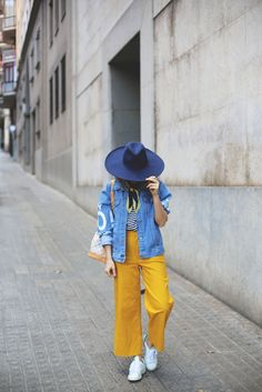 The Best Blogger Street Style for Spring Outfit Inspiration | @myshowroom in navy hat, denim jacket, striped blouse, handkerchief, marigold slacks, and white sneakers