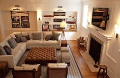 family room layout/ OR basement Giannetti Home: Comfy, cozy living space with with modern gray linen sectional sofa, tobacco leather ottoman tv above fireplace