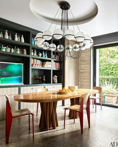 In the kitchen's dining area, a vintage Gino Sarfatti chandelier is installed above a table by Martin Szekely and chairs by Jean Prouvé for Vitra; a photograph by Wolfgang Tillmans and a collection of 1920s Robj porcelain decanters are arrayed on the shelves.