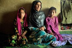 Siblings Azizullah, 18, Shukria, 16, and Rahmatullah, 10, are sitting close to their mother, Najiba, on the floor of their one-room house in Jawzjan, Afghanistan. The floor is made of mud but very little of it shows. Plastic rice bags, ripped wide open to serve as carpets, cover almost all of it. This bare-bone house, bought with the dowry money Najiba received when her eldest daughter got married, is all this family has.