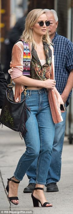Funky look: J-Law, 23,was dressed in skinny jeans and a pink velour jacket over a patterned shiny vest. She wore black sandal heels that revealed her black toenail polish