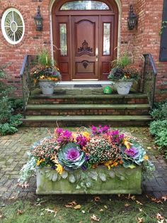"""Filling containers with natural autumnal textures can bring a pop of color to your doorstep and reflect an inviting atmosphere,"" Rose says. For this exterior, she added a third planter in addition to the two on either side of the door. The low arrangement puts the focus on the different colors and textures within."