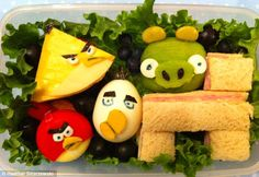 A kiwi, an egg, a Babybel cheese, a ham sandwich make a sweet scene of farmyard animals including a chicken and a rooster