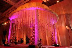 traditional vedi , orange canopy , pink and orange mandap , pink flower draped pillars , orange genda flowers hanging , golden huge matkas