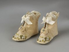 1880/1888: Pair of boots for a baby, cream silk with bows and floral embroidery, made in France, 1880-1889. Silk embroidered in coloured silks.