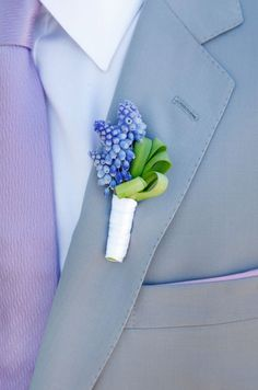 The groom's boutonniere, of grape hyacinths tied with a white ribbon, accents his light purple tie.