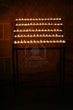 Closeup of rows of votive prayer candles in a dimly lit church.