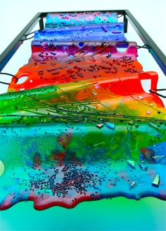"Artist: Lisa Mote - ""Rainbows Reflection: Fused, textured, and slumped glass, dimensions 15"" x 40"" x 4"". Glass is suspended within a metal frame in order to elevate away from the wall. Photographed from a lower angel in order to detail the texture, and the ripples in the glass. All elements created by the artist.""  #artsintheheart #fusedart #glassart"