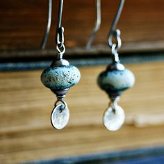Sky-blue handmade lampwork glass beads are suspended above texture hammered sterling silver discs.