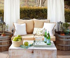 You don't need vast amounts of space to create a comfortable outdoor room. Here, a love seat, rustic barrel side tables, and a trunk create the perfect small outdoor space. Drapery behind the love seat also helps define the space and softens the entire look.