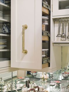 """In designer Stephanie Stokes's 48-square-foot New York City kitchen, the """"pantry"""" for dry goods consists of two cabinets that slide out over the countertop so that everything is easy to find.   - HouseBeautiful.com"""