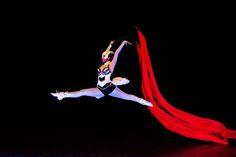 Ballet dancer with ribbon under UV light. Crystal Light Show.