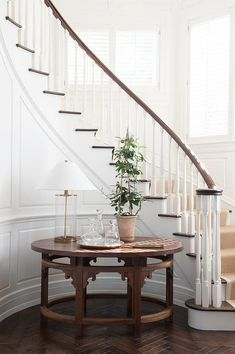 foyer features a curved staircase wall clad in wainscoting lined with a round table topped with a Ralph Lauren Home Modern Accent Lamps atop a wood herringbone floor. Foyer Staircase, Entryway Stairs, Curved Staircase, Entry Foyer, Staircase Design, Staircase Decoration, Staircase Handrail, Interior Staircase, Bannister