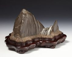 Suiseki or scholar s stone in the form of a mountain peak with snowy seams, the origin of waterfalls, rising from a collar of clouds. Of Furuya type, grey-black stone with white quartz inclusions; on a finely carved and polished rosewood stand.
