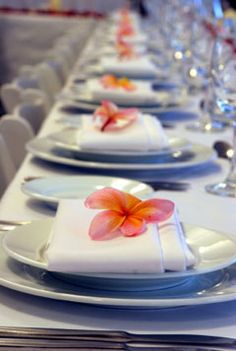 #coral wedding tables ... Simple wedding reception ideas using napkins and pink frangipani's.  If we have enough flowers we could lay them on top of napkins/possibly every other one if not enough flowers....something to think about