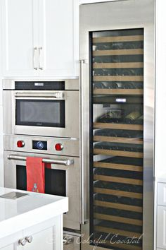 Sub-Zero wine column, and  Wolf ovens in a coastal white kitchen.  Appliance wall  @becolorfulcoastal.com http://www.becolorfulcoastal.com/2017/02/a-coastal-kitchen-reveal.html