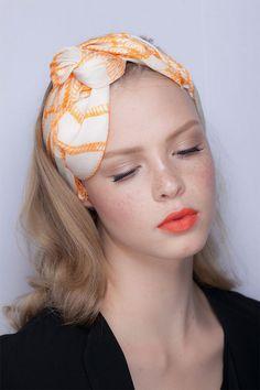 Pele: Blush rosa e iluminador.  Olhos: Cílios postiços, rímel e sombra marrom suave. Sobrancelha levemente marcada.  Boca: Batom laranja.