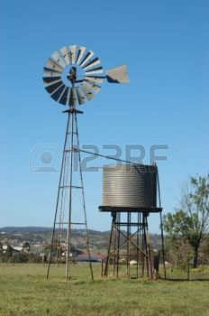 windmill: Windmill and tankstand in paddock, Queensland, Australia. Windmills are commonly used for pumping water from bores or dams to troughs for livestock.