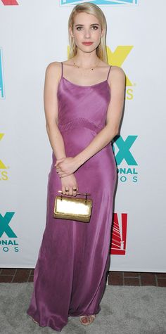 Emma Roberts tapped into the '90s and wore a violet satiny long slip dress to the 20th Century Fox Comic-Con party, accessorizing with gold Jennifer Meyer jewelry, a gold M2Malletier top-handle clutch, and nude Kurt Geiger London sandals.