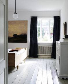 A bedroom in Sweden with white painted floor and black curtains; via My Scandinavian Retreat.