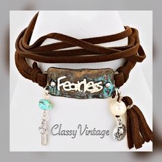 """Dark brown faux leather wrap """"Fearless"""" bracelet. Dark brown faux leather wrap bracelet with """"fearless """" logo. 26 inches in length with a 2 inch extender. The logo is a large 1.5 inches long and 3/4 inch high. . Chrystal center in each arrow and charms dangling below. Boutique Jewelry Bracelets"""