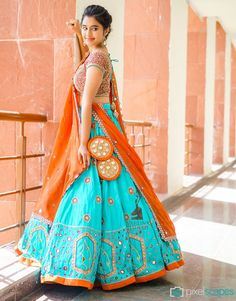 Turquoise and orange chaniya choli A Beautiful Blue Orange Lehenga is in Raw silk, the fabric looks royal and classy and is traditionally, culturally woven. Choli Designs, Lehenga Designs, Blouse Designs, Indian Attire, Indian Wear, Indian Dresses, Indian Outfits, Indian Clothes, Orange Lehenga