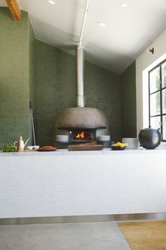 the wood oven takes on a modern and almost soothing look with the muted colors of the surround and the soft green of the tiles